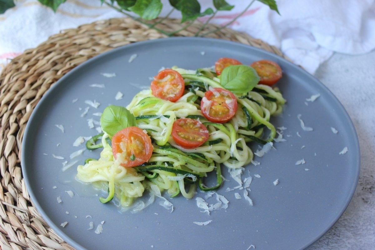 Emplatado de los espaguetis de calabacín una vez salteados con tomates cherry y queso parmesano