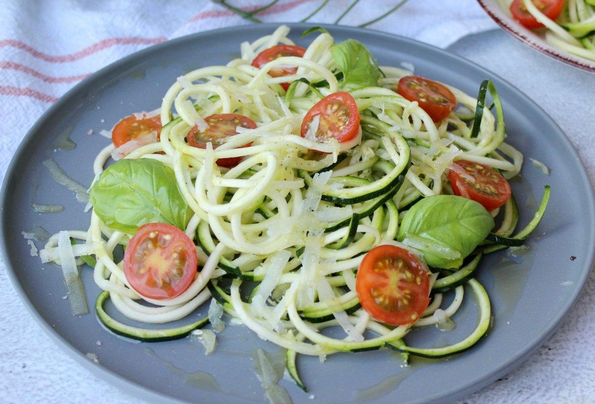 Emplatado y presentación final de los espaguetis de calabacín crudos con tomates cherry y queso