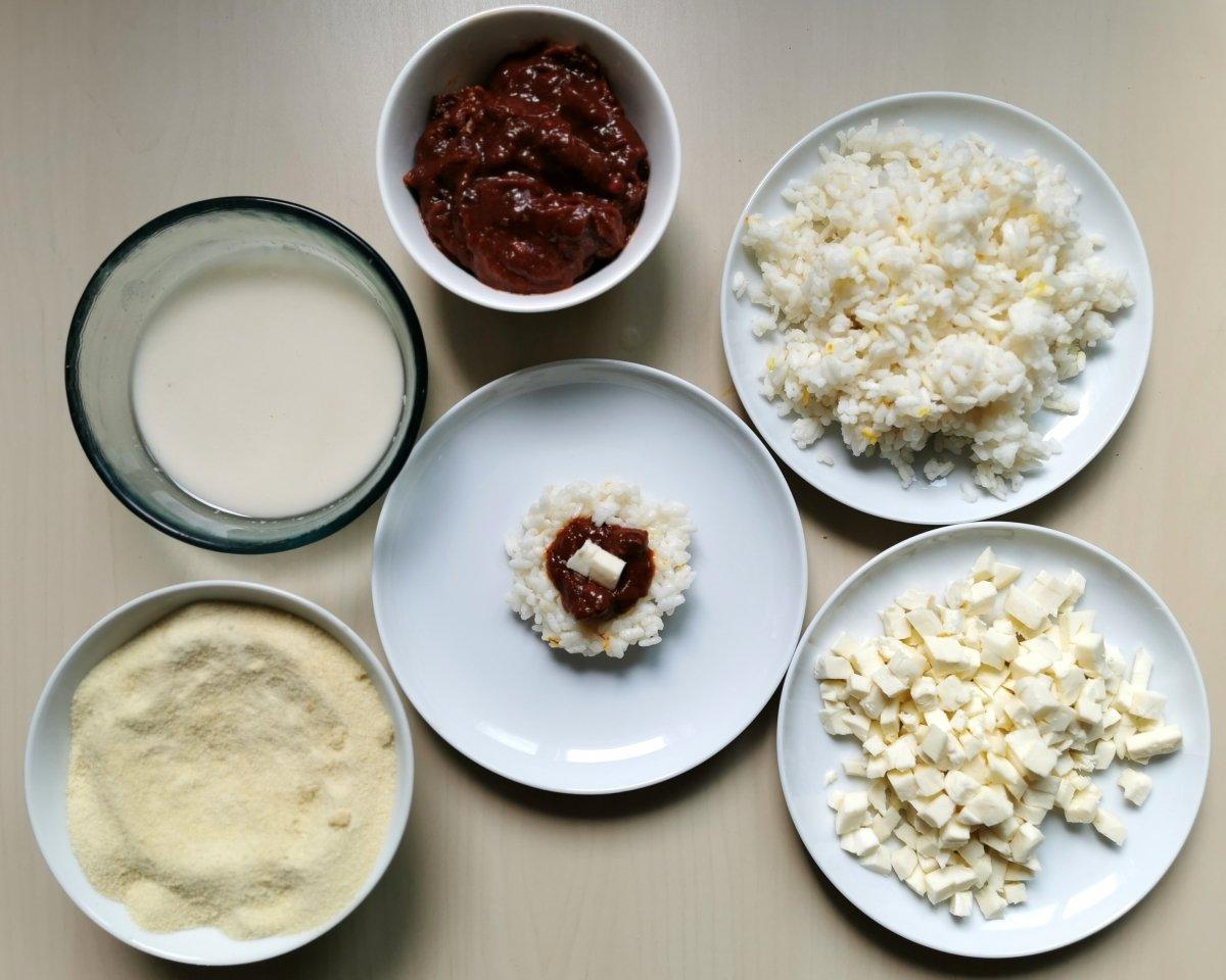 Ensamblar los arancini: En el medio del arroz poner un poco de salsa y unos daditos de mozzarella.