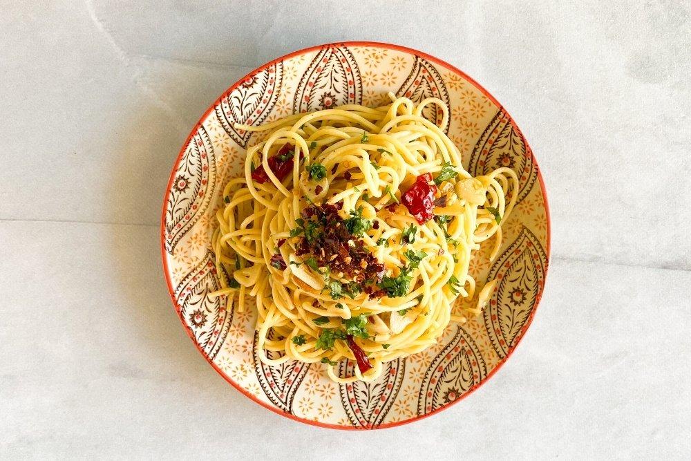 Espaguetis aglio e oleo decorado con escamas de pimiento y perejil