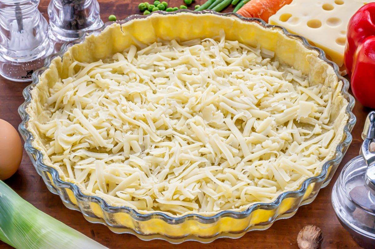 Espolvorear el queso rallado dentro de la quiche