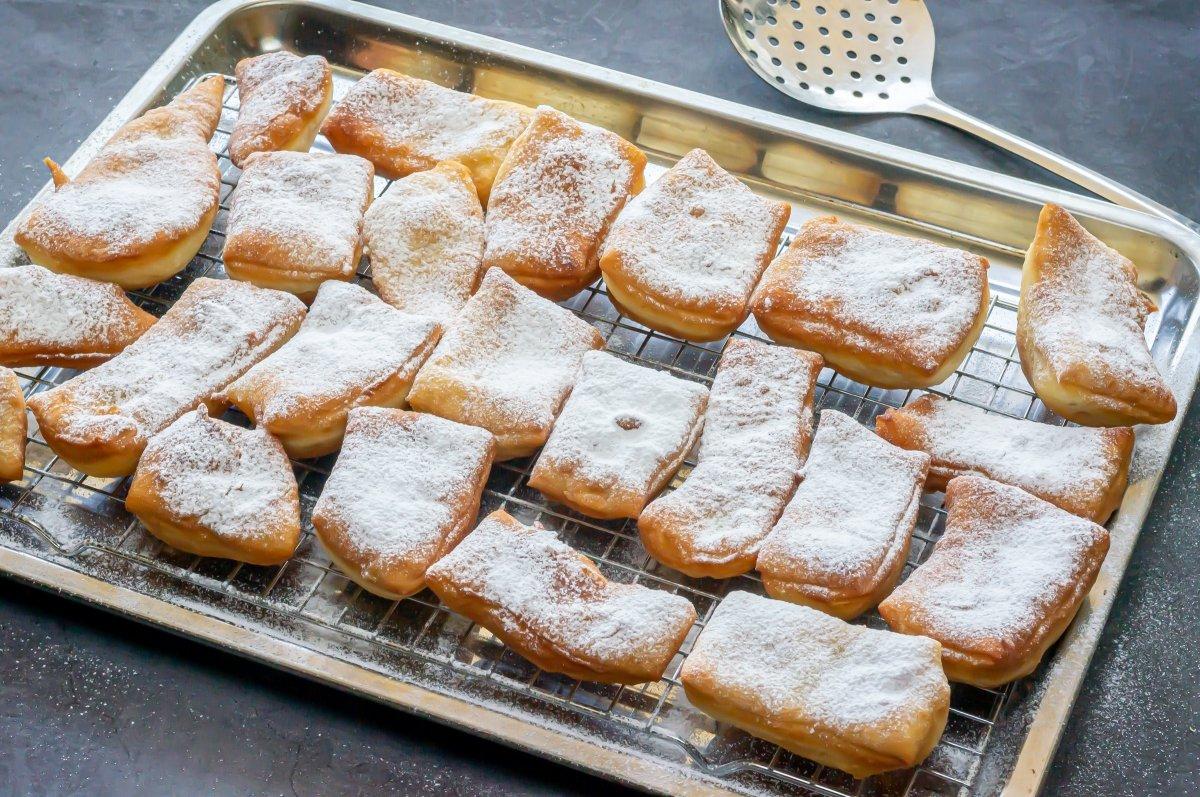 Espolvorear las beignets con mucho azúcar glas