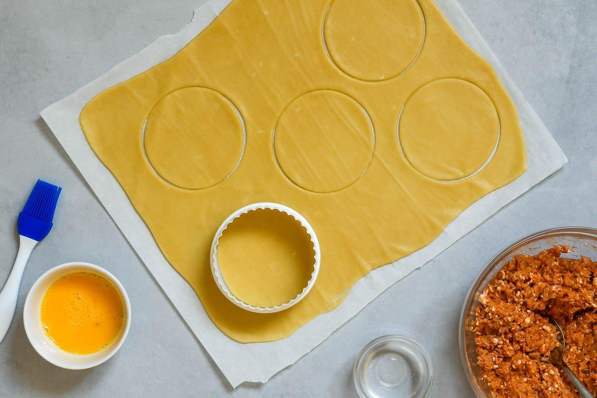 Estirar la masa de empanadillas con un rodillo y cortar
