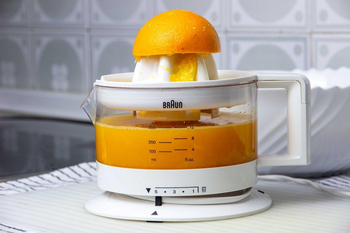 Exprimir el zumo de las naranjas para la macedonia de frutas