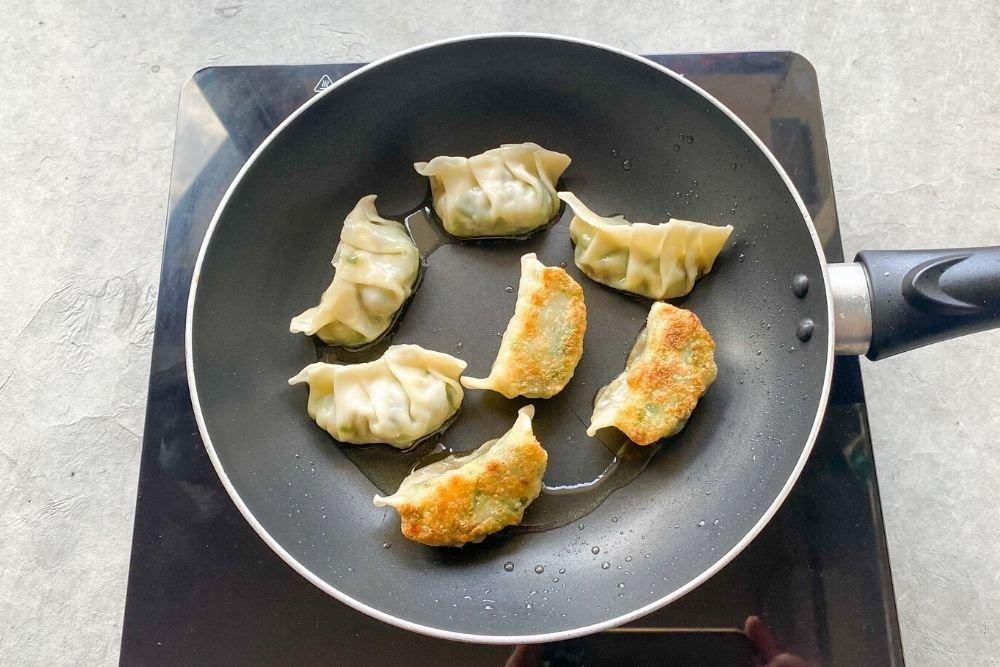 Freír y después cocinar al vapor las gyozas tradicionales