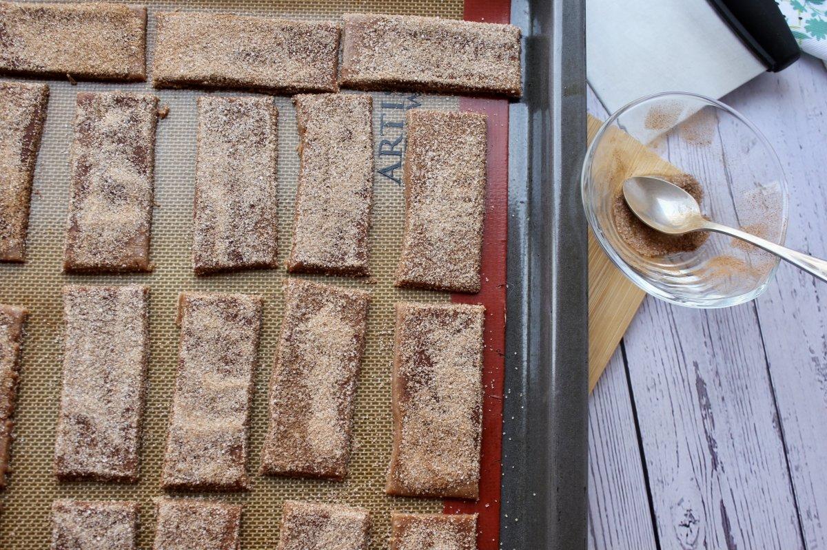 Galletas de canela sobre silpat acabadas de espolvorear con azúcar y canela previo su horneado