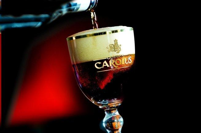 Gouden Carolus Classic vertida en un vaso con el logo de la cerveza