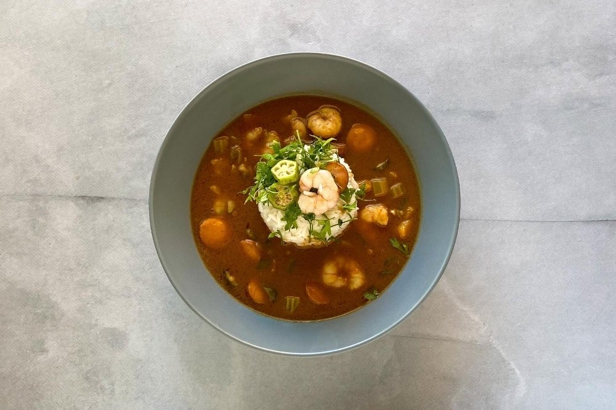 Gumbo con arroz decorado con perejil, gambas y okra