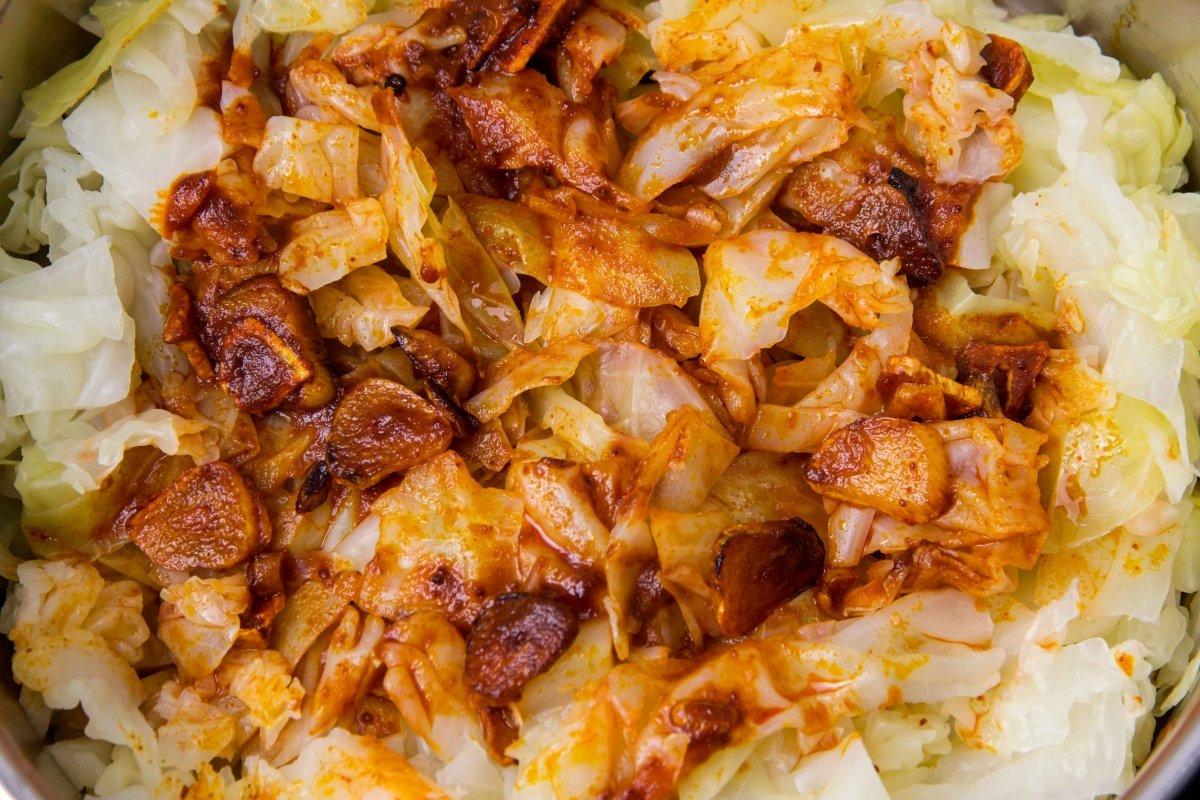 Hacer un refrito de ajos y pimentón y añadir a la berza o el repollo