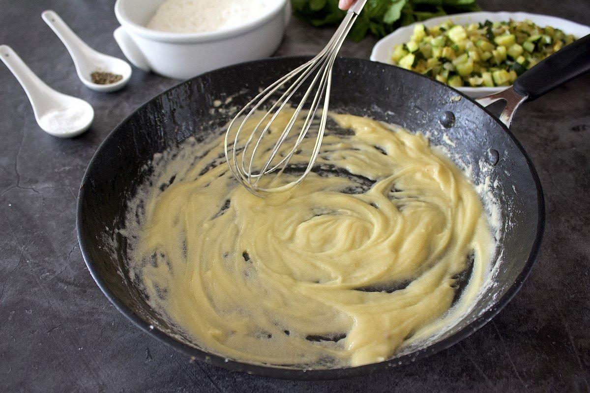 Harina de las croquetas de calabacín añadida a la sartén