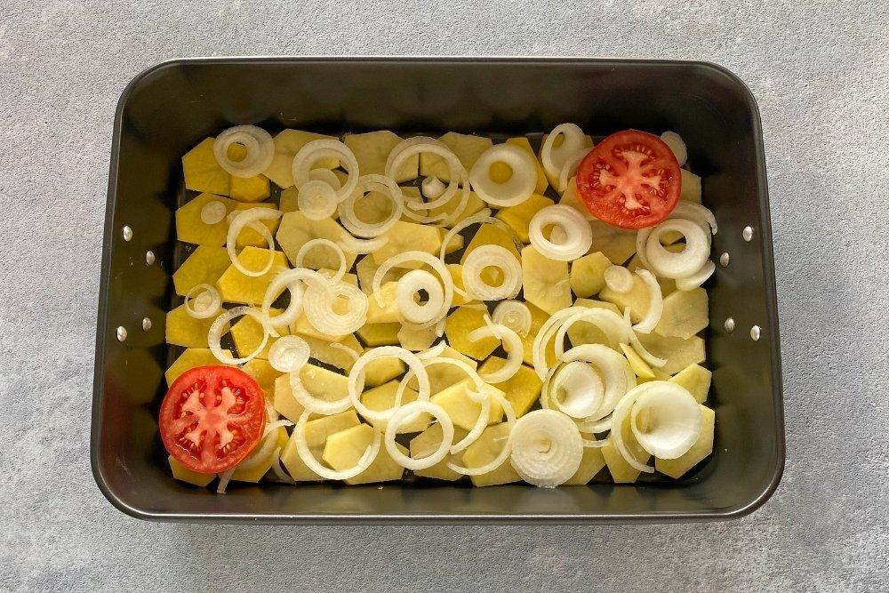 Hornear las patatas, la cebolla y el tomate