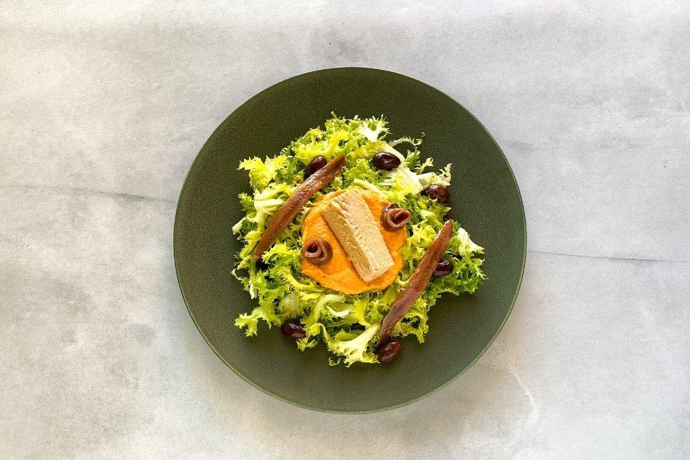 Incorporar el atún, las anchoas y las aceitunas negras en la ensalada xató