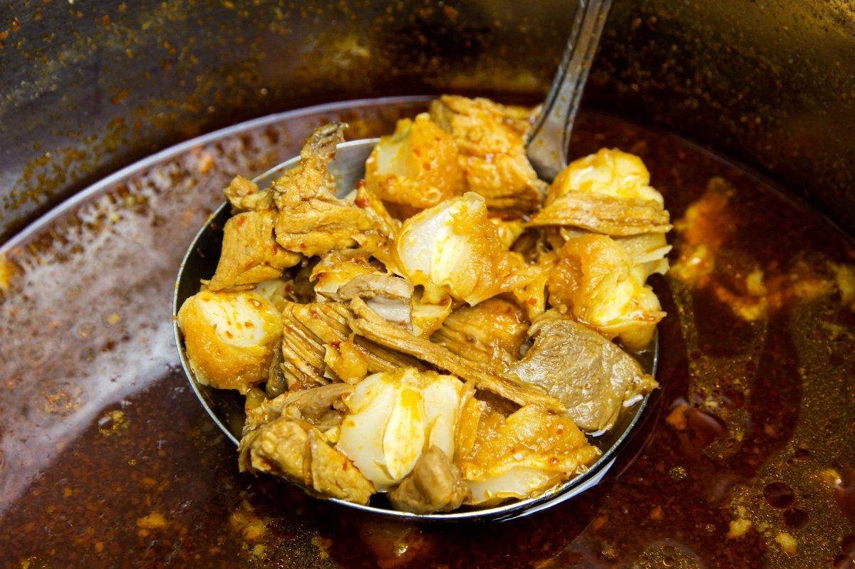 Incorporar el mote de maíz para el pozole rojo y cocinar 10 minutos