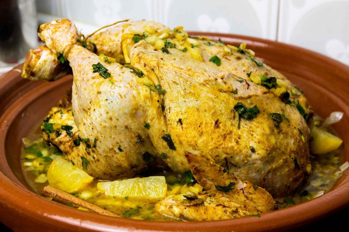 Incorporar el pollo marinado, los limones, el agua y la canela al tajín