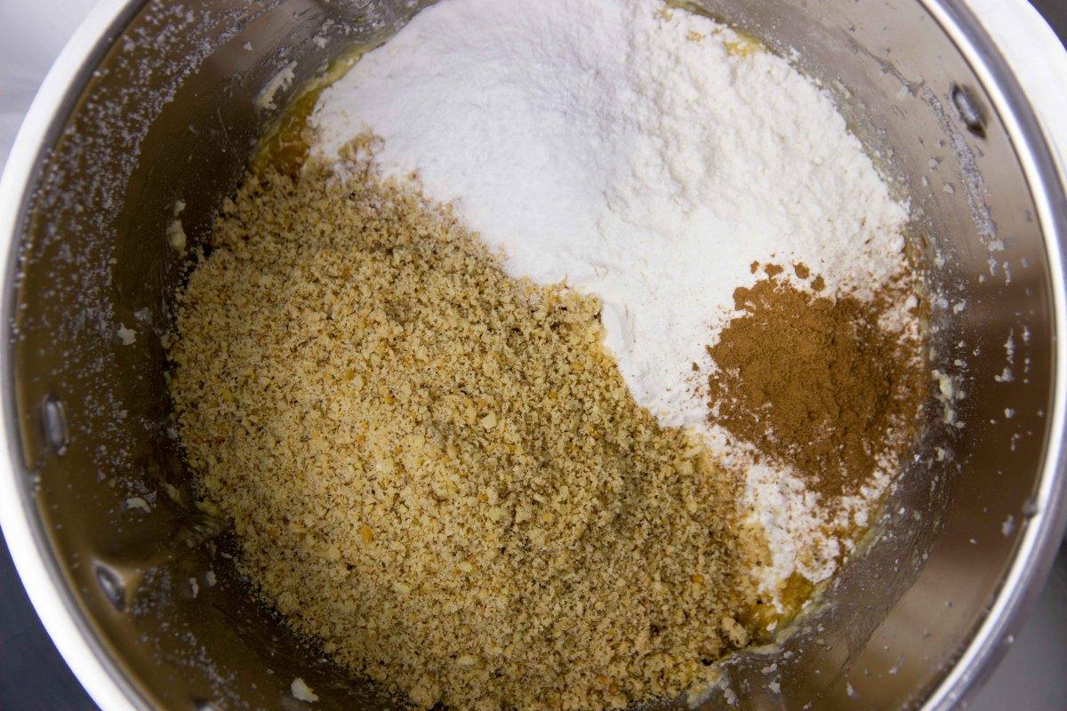 Incorporar la harina, la avellana, la canela y la levadura a la masa del bizcocho de manzana