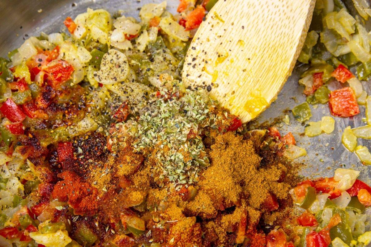 Incorporar las especias y el vino blanco a las verduras para hacer la salsa de las manitas