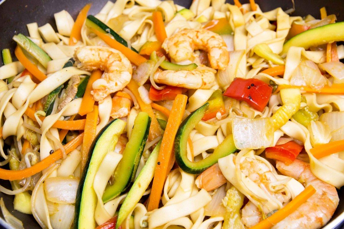 Incorporar los tallarines al wok y saltear todo a potencia máxima para servir