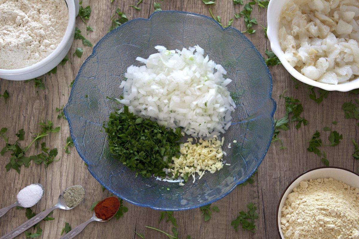 La cebolla, el perejil y el ajo picados de las tortillitas de bacalao