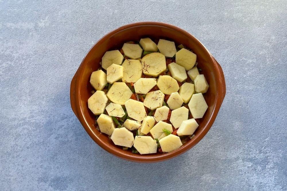 Laminar las patatas e introducirlas a la cazuela junto a unas hebras de azafran