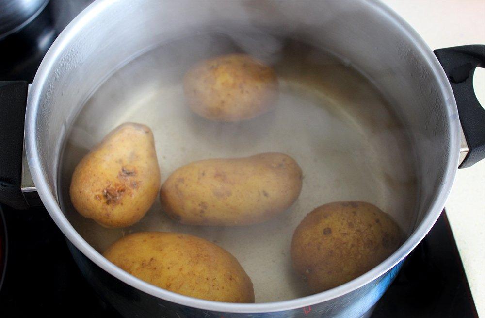Las patatas de las patatas aliñadas con bacalao cociéndose