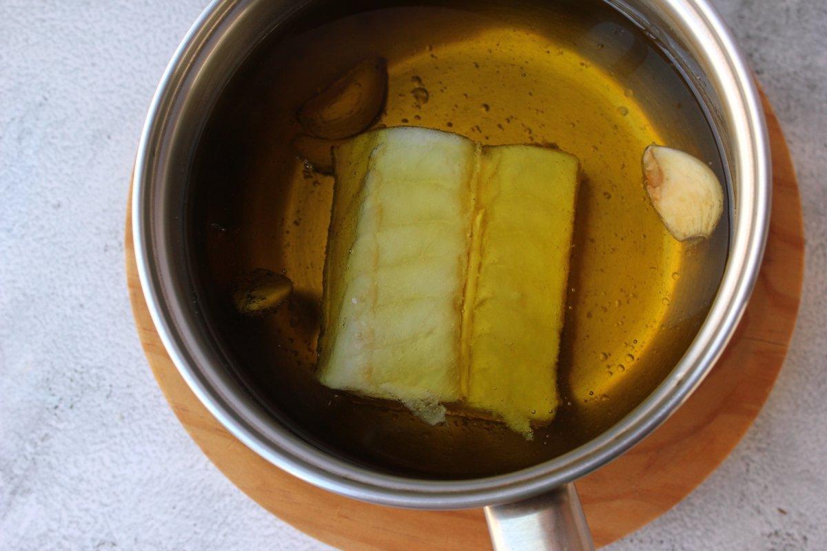 lomo de bacalao sumergido en aceite de oliva virgen extra para ser confitado a baja temperatura
