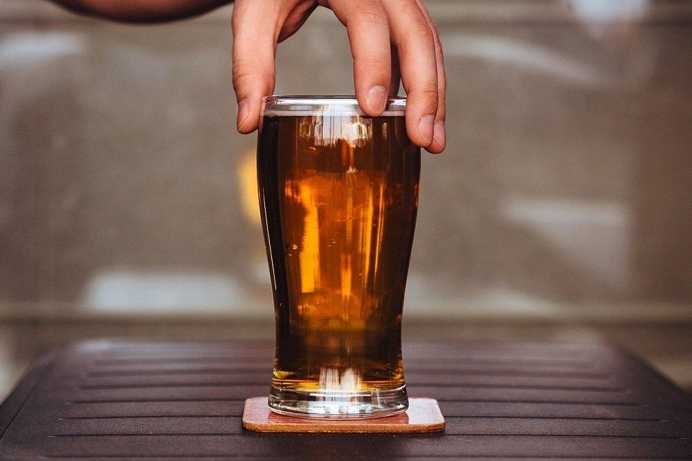 Mano sosteniendo un vaso de cerveza
