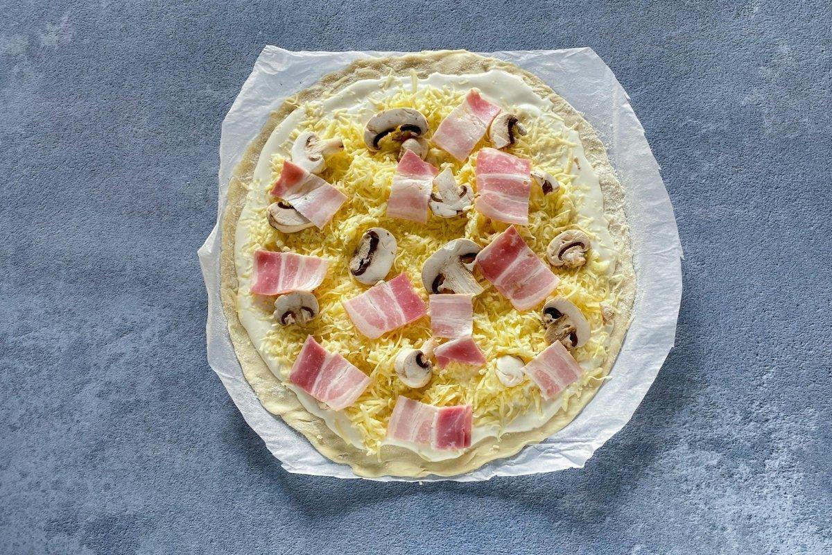 Masa de pizza con bacon y champiñones laminados