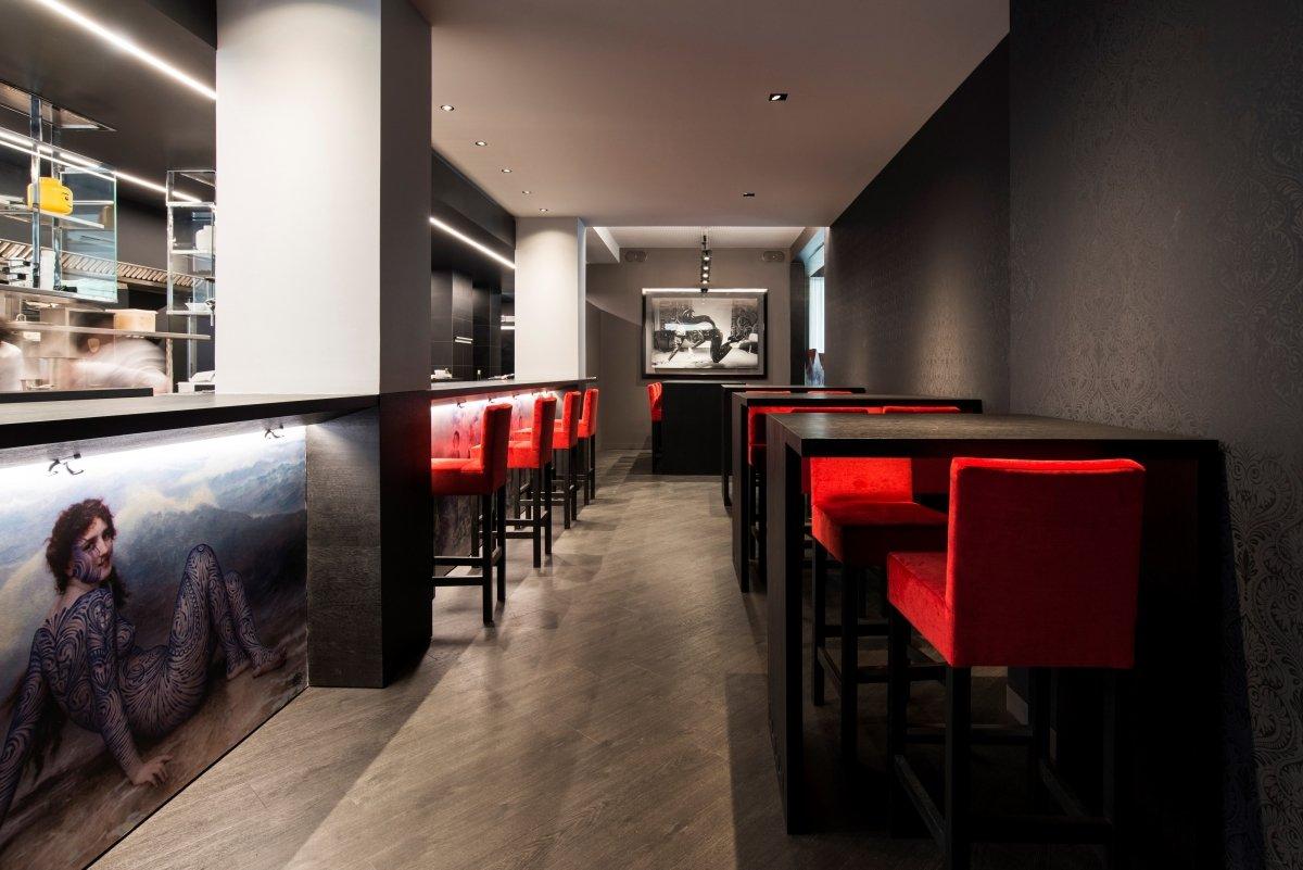 Mesas altas frente a la barra del restaurante Tatau Bistró