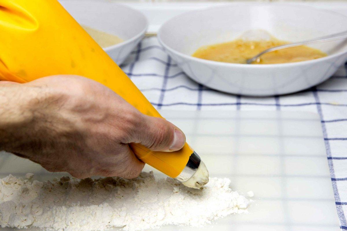 Meter la masa en la manga para hacer las croquetas de boletus