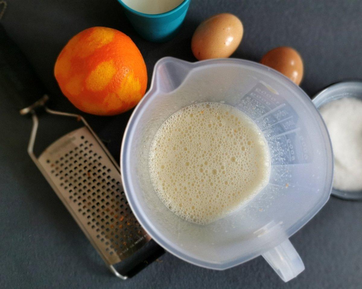 Mezclar con la batidora los huevos, el azúcar restante (40 g), la leche y la ralladura de las dos na