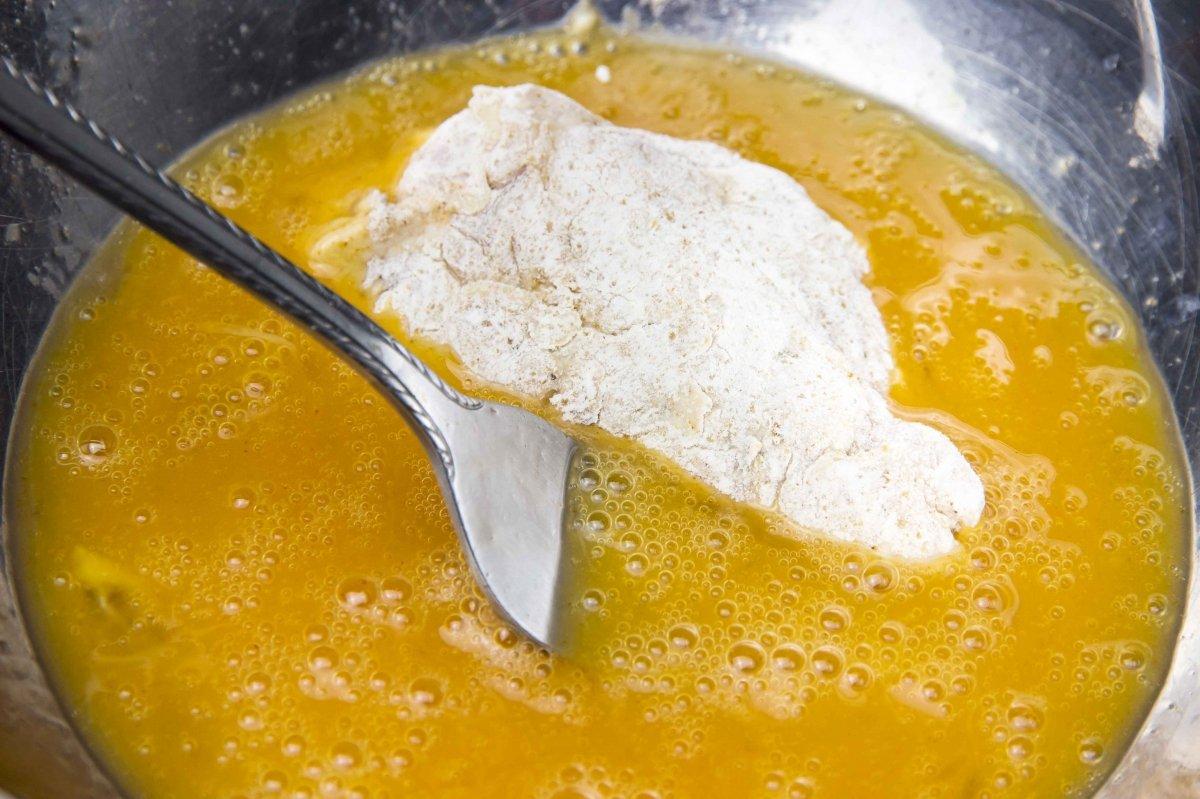 Pasar el pollo por huevo para hacer el pollo frito estilo cajún
