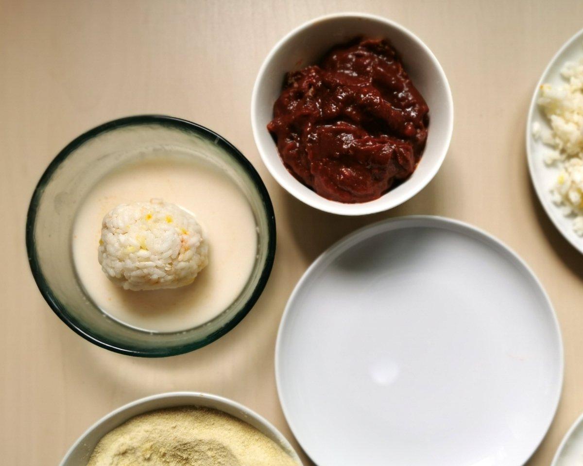 Pasar la bola de arroz en la masa de harina y agua.