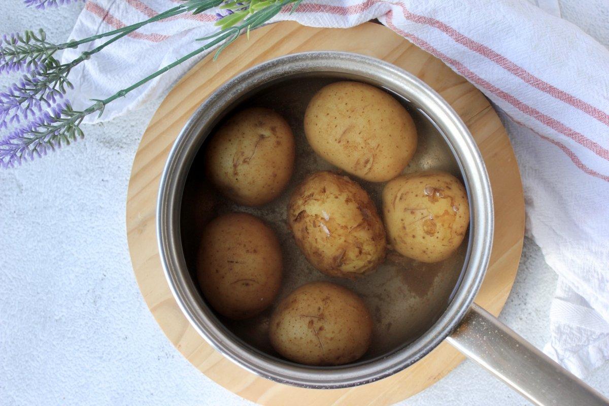 patatas con piel dentro de un cazo cubiertas con agua para ser cocidas