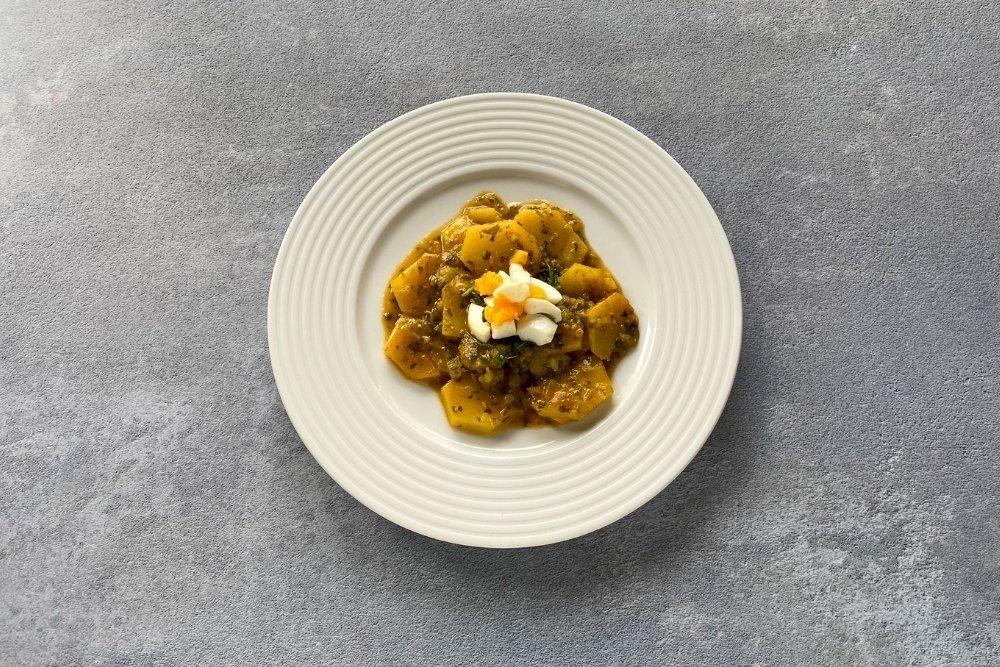 Patatas en salsa verde decoradas con huevo duro