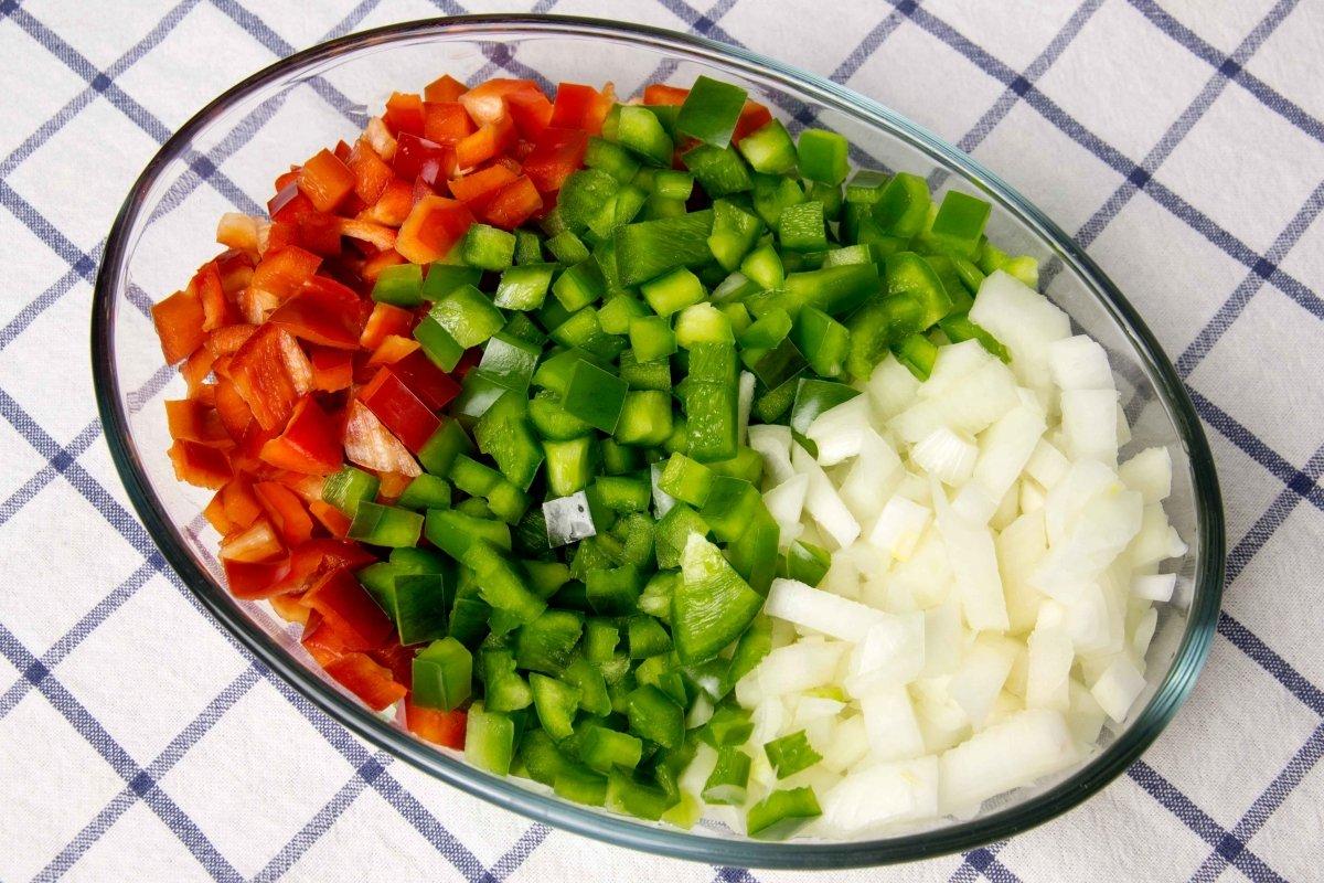 Picar las cebollas y los pimientos para el pisto manchego