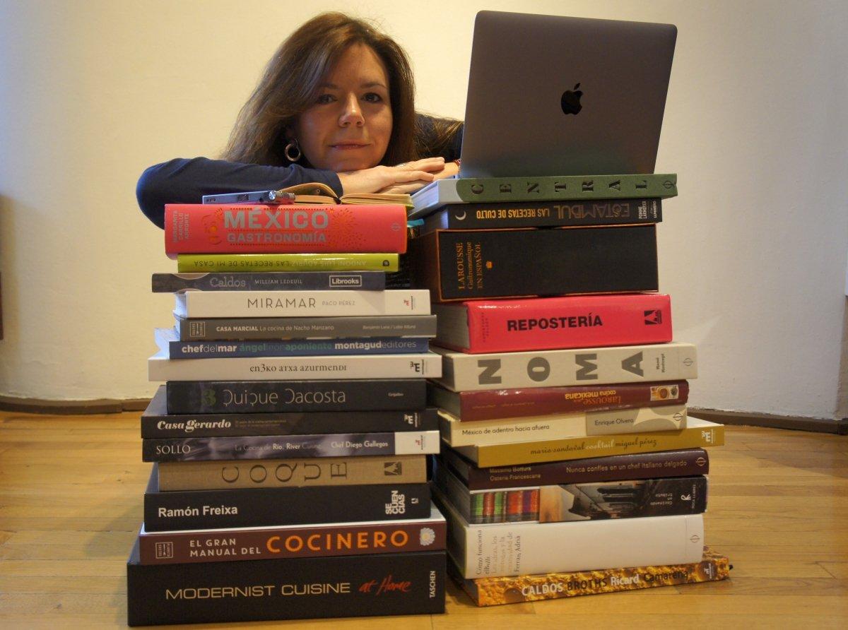 Pilar Salas junto a un ordenador y montones de libros