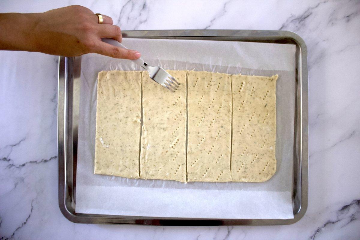 Pinchando la masa de las tostas con salmón y queso