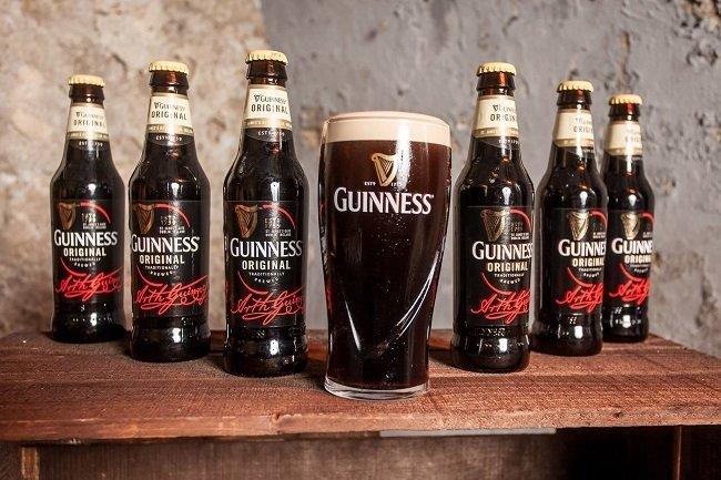 Pinta de cerveza Guinness rodeada de varias botellas de la marca