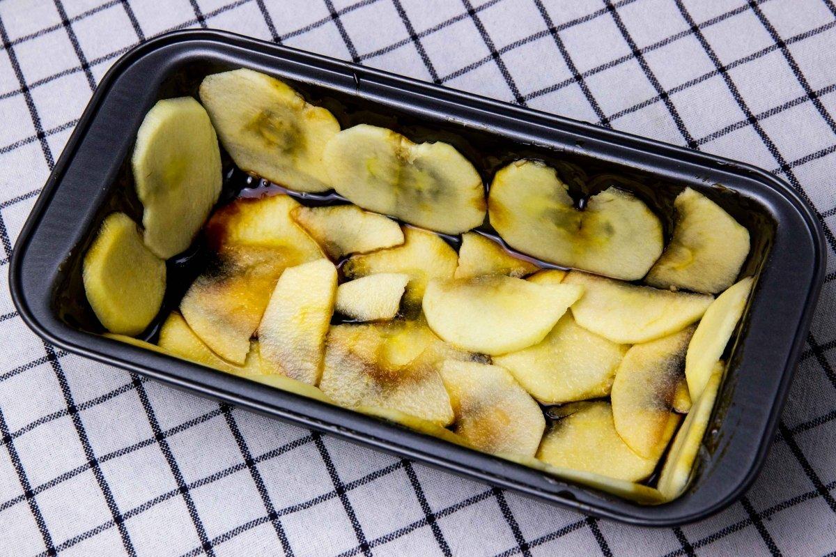 Pintar el molde de caramelo y forrarlo de manzana para hacer el bizcocho