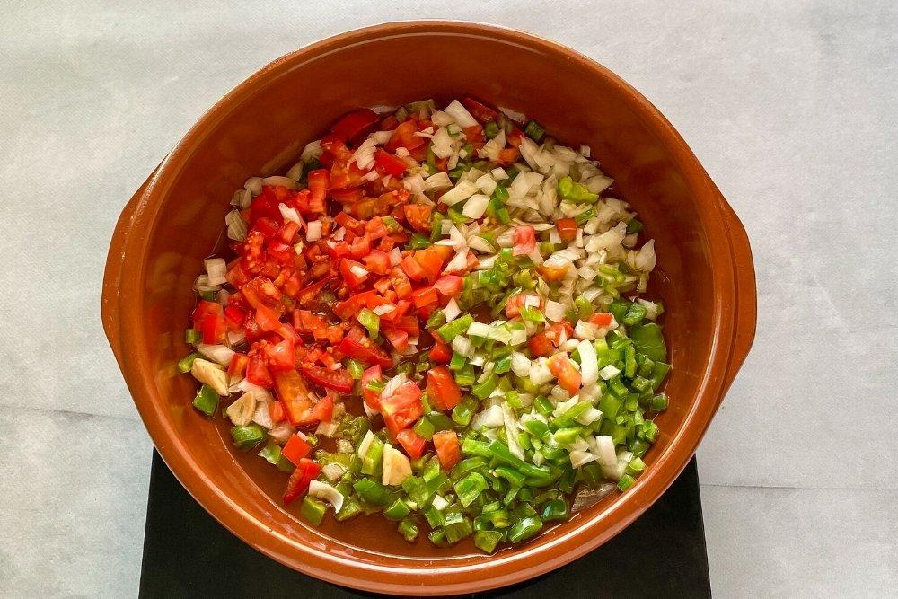 Pochado de cebollas, ajo, pimiento verde y tomate