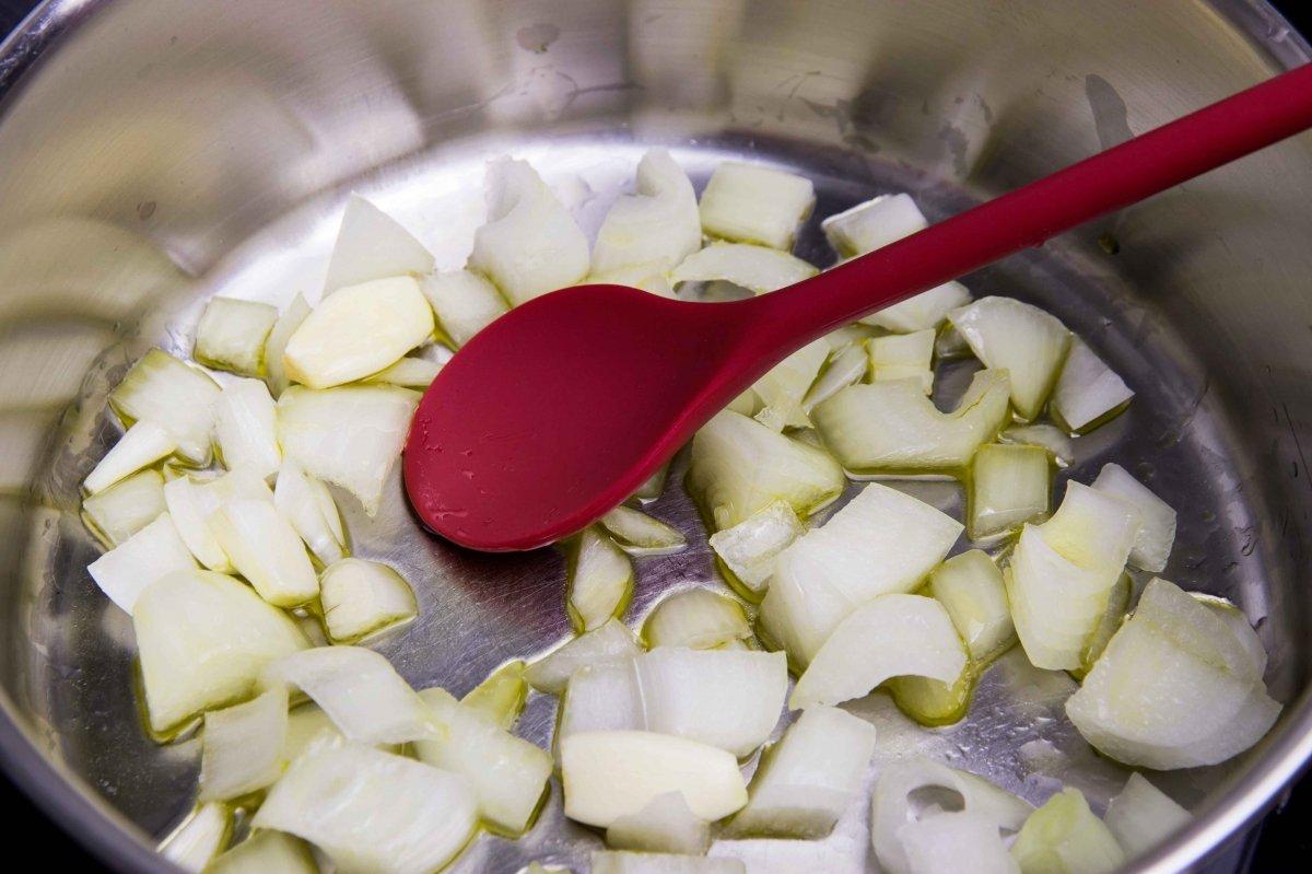 Pochar la cebolla y los dientes de ajo para la crema de calabaza con avellanas