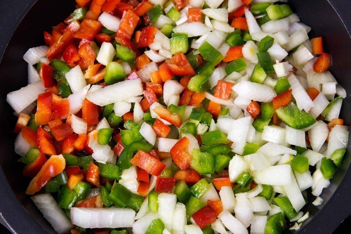 Poner a pochar los pimientos y las cebollas para el pisto manchego