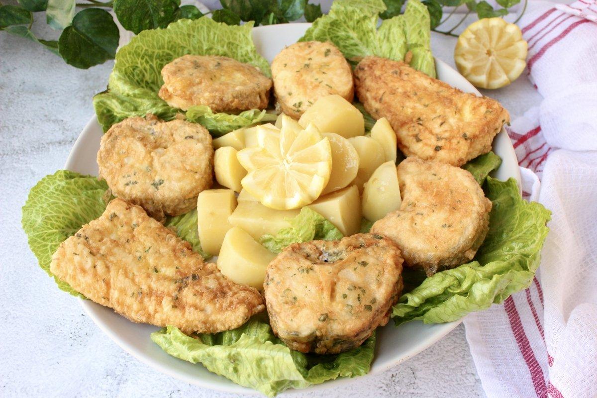 presentación final del emplatado de la merluza a la romana con patatas cocidas