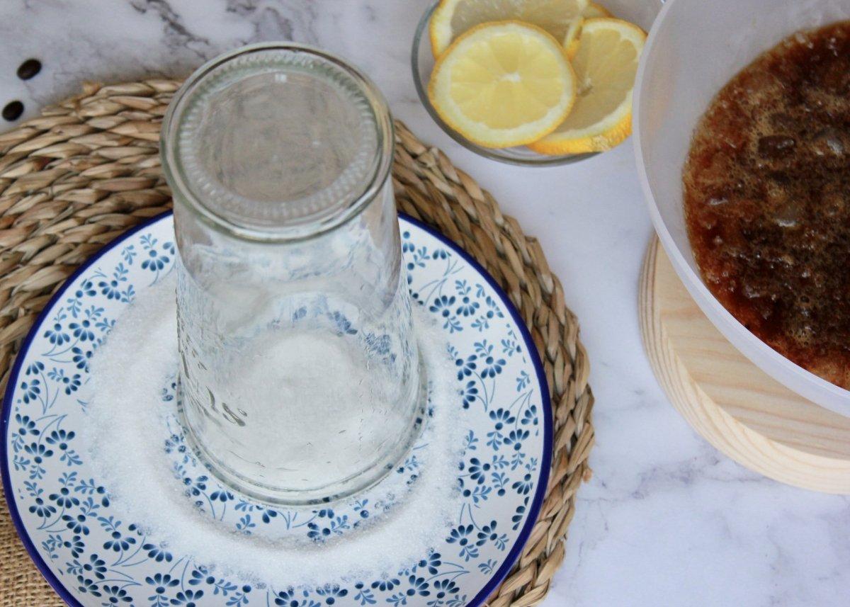 Proceso de decoración del borde del vaso con zumo de limón y azúcar