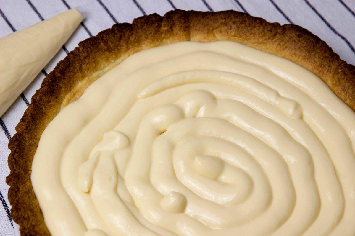 Rellenar la base de la tarta de frutas con crema pastelera