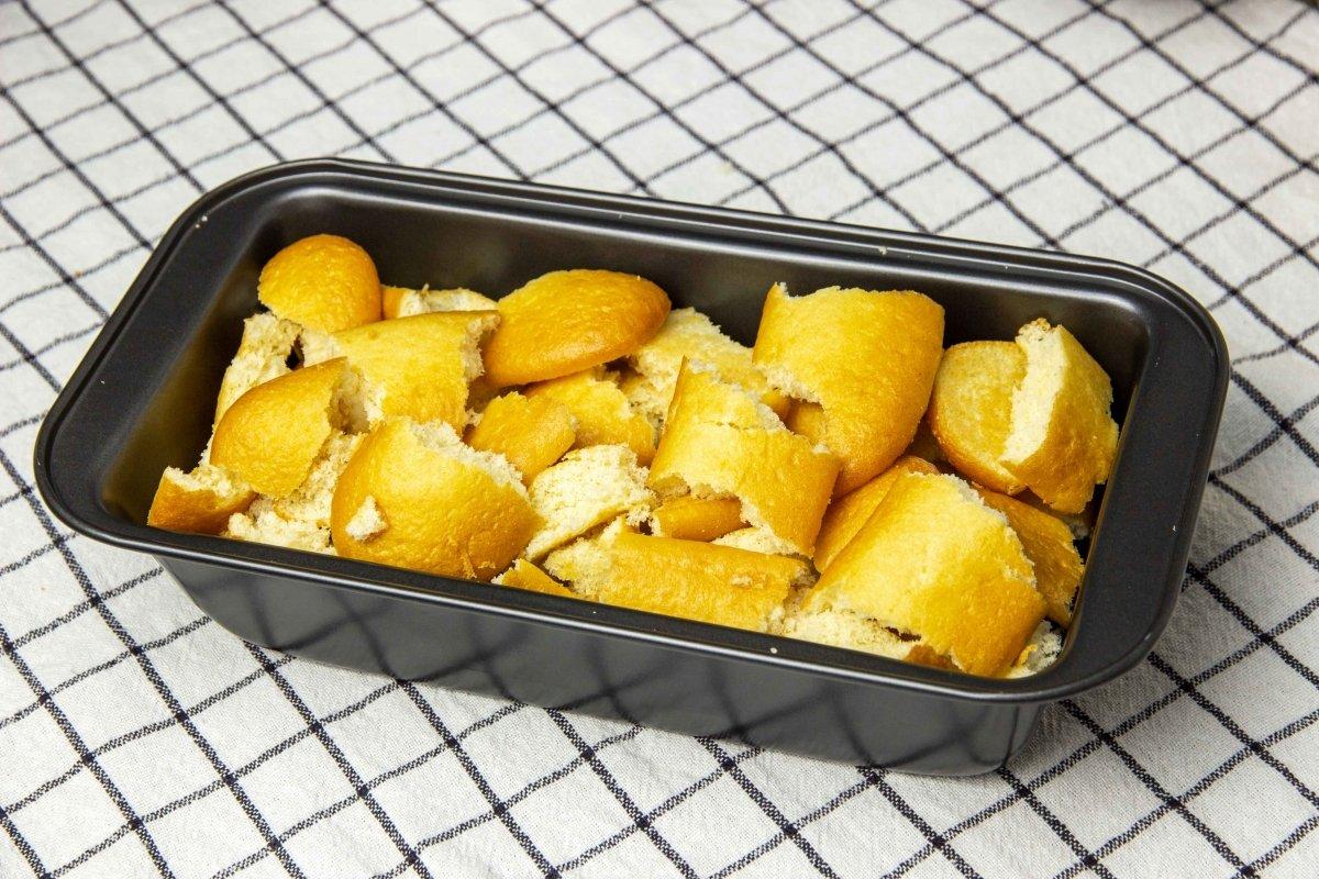 Repartir caramelo y bizcochos por el molde para hacer el pan de Calatrava