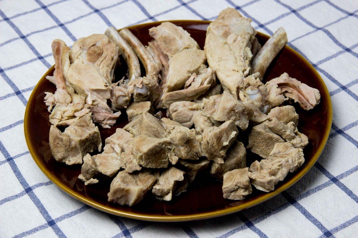 Sacar carnes del caldo y cortarlas para añadir después al pozole rojo
