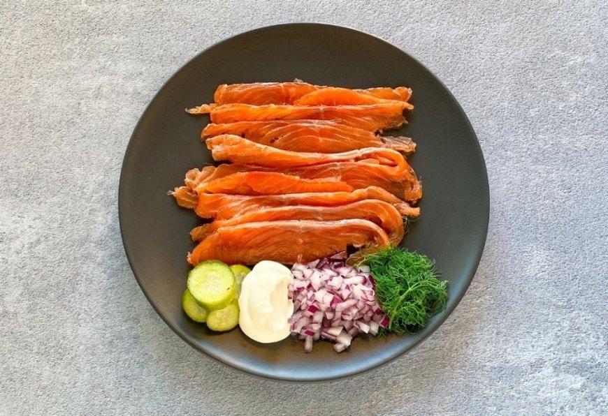 Salmón marinado acompañado de pepinillos, crema agria, cebolla roja y eneldo