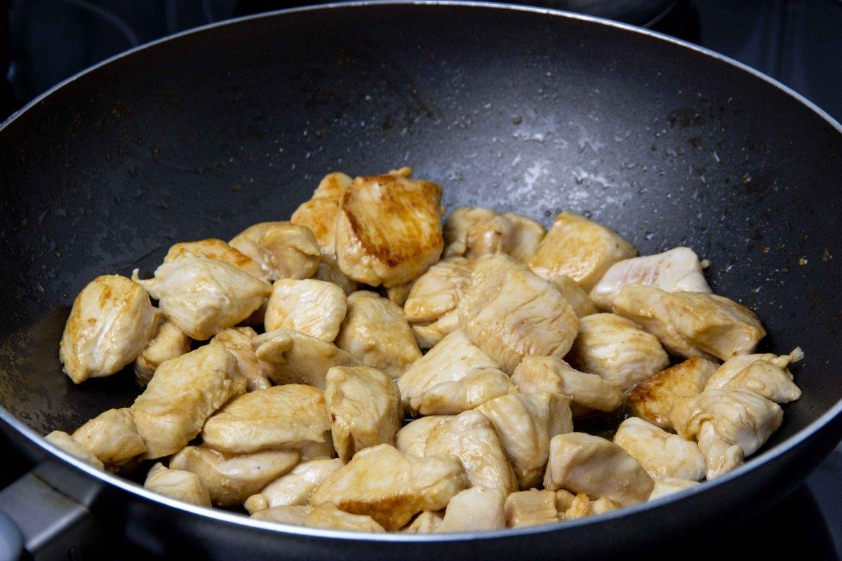 Saltear el pollo para el chop suey en el wok