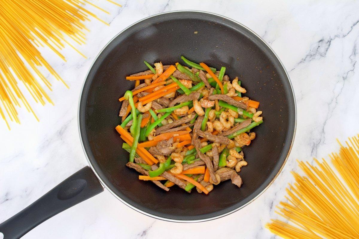 Todos los ingredientes de los tallarines chinos con verduras, carne y gambas añadidos en el wow
